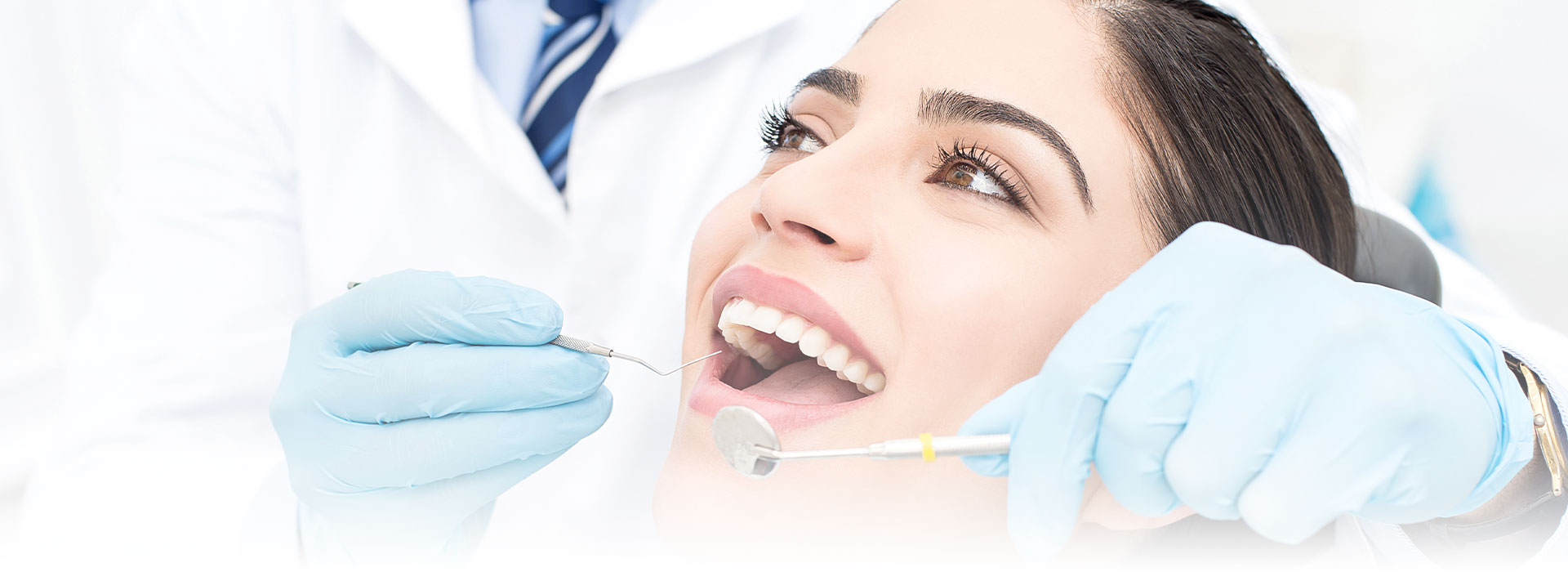 Woman smiling while having dental surgery at the crestwood dental group